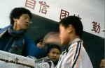 A teacher, Ms Zhang, slapping a student in the face at her class. The Chinese characters on the wall say 'self-confidence', 'being united as one' and 'diligence'. (From the internet)